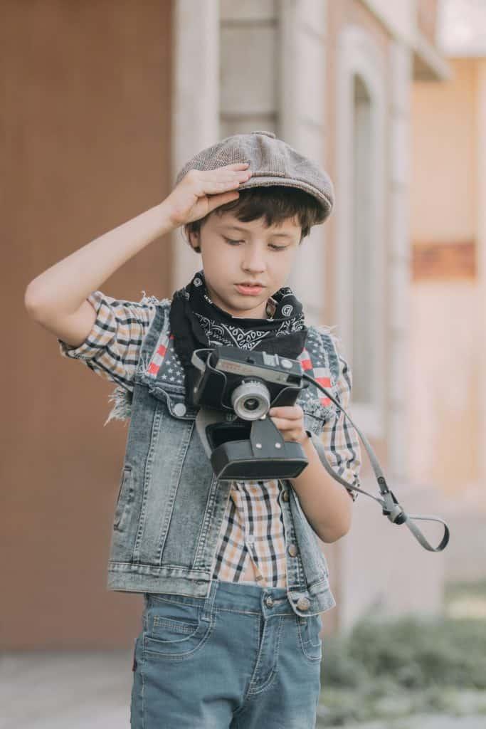 Skinny kid holding a camera